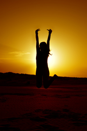 positive feelings: a young woman jumping in backlight at sunset