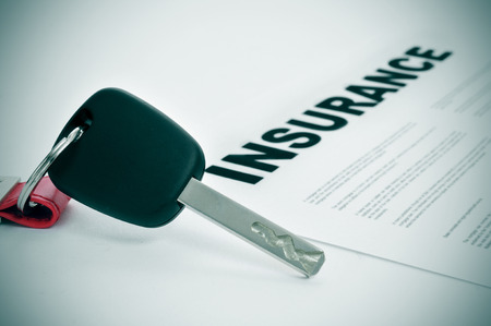 closeup of a car key and a insurance policy on a white surface