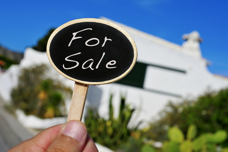 a man hand holding a signboard with the text for sale written in it in front of a house photo