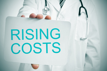a doctor showing a signboard with the word rising costs written in it