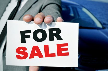 car retailer: man in suit holding a signboard with the text for sale written in it, with a black car in the background