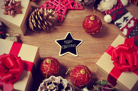 center table: a pile of gifts and christmas ornaments, such as christmas balls and stars, on a rustic wooden table with a heart-shaped chalkboard with the text merry christmas in the center Stock Photo