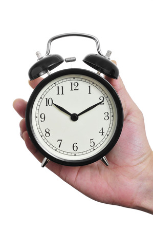 winder: a man hand holding a typical mechanical alarm clock on a white background