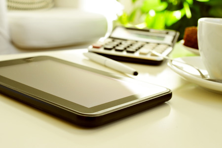 detail of a desk with a tablet, a calculator and a cup of coffee or tea in an office with a nice atmosphere photo