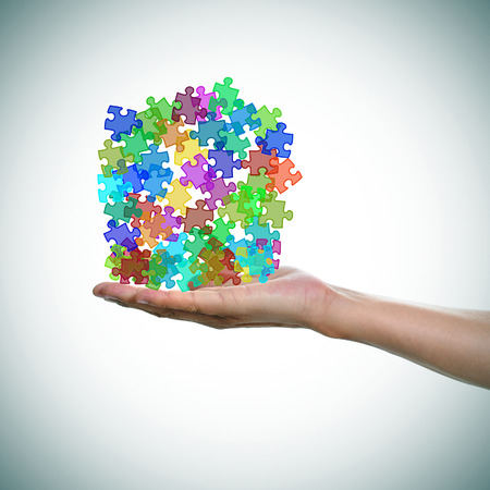 a man hand with a pile of puzzle pieces of different colors as the symbol for the autism awareness Stock Photo