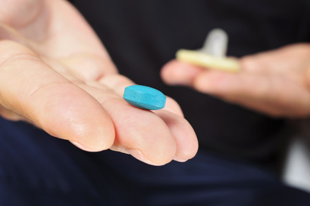 sexual intercourse: closeup of a young man with a blue pill in one hand and a condom in the other hand Stock Photo