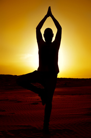 yoga sunset: a young man practicing the yoga tree pose in backlight at sunset