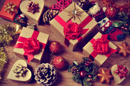 a pile of gifts and christmas ornaments, such as christmas balls, stars and tinsel, on a rustic wooden table Stock Photo
