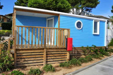 nice accommodations: a nice blue mobile home with a wooden veranda in a campsite