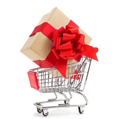a cardboard gift box with a red ribbon bow in a shopping cart on a white background photo