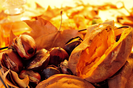 tots: some roasted chestnuts and sweet potatoes in a basket with autumn leaves Stock Photo