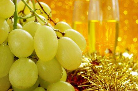 closeup of a bunch of grapes and glasses with champagne in the background for the traditional celebration of the New Year in Spain 스톡 콘텐츠