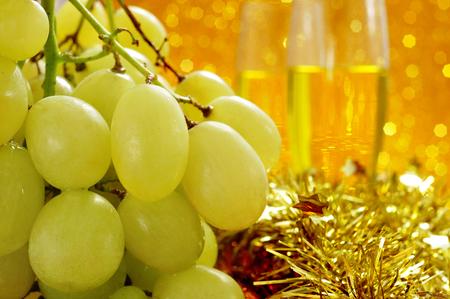 racimos de uvas: primer plano de un racimo de uvas y copas con champ�n en el fondo de la tradicional celebraci�n del A�o Nuevo en Espa�a