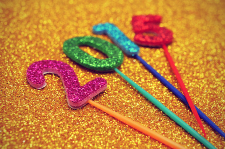 glittering numbers of different colors forming the number 2015, as the new year, on a shiny golden background photo