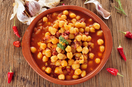 spanish home: an earthenware bowl with potaje de garbanzos con jamon, a spanish chickpeas stew with ham, on a rustic wooden table