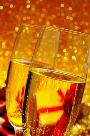 closeup of two glasses with champagne on a festive and shiny golden background photo
