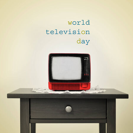 old fashioned tv: an ancient red television on a table and the sentence world television day on a beige background, with a retro effect