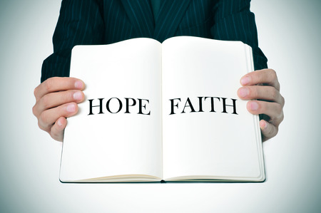 man showing an open book with the words hope and faith written in its pages photo