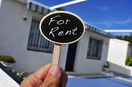 a man hand holding a signboard with the text for rent written in it in front of a house photo