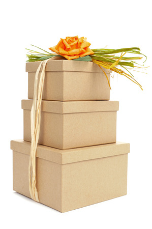 some gift boxes tied with natural raffia of different colors and topped with a flower on a white background photo