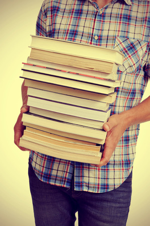 young man carrying a pile of books, with a filter effect photo