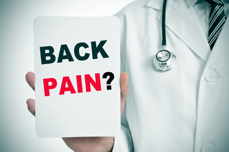 spinal disc herniation: a doctor showing a signboard with the question back pain? written in it