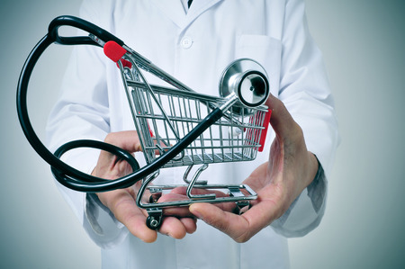 healthcare office: doctor holding in his hand a shopping cart with a stethoscope inside, depicting the health care industry concept