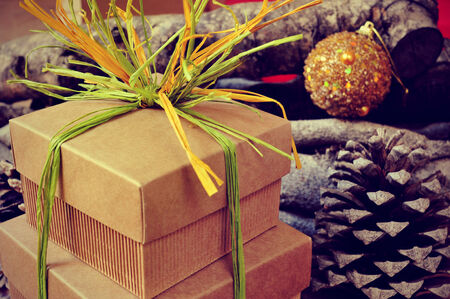 pinecones: some gift boxes tied with natural raffia of different colors with christmas balls, pinecones and logs in the background