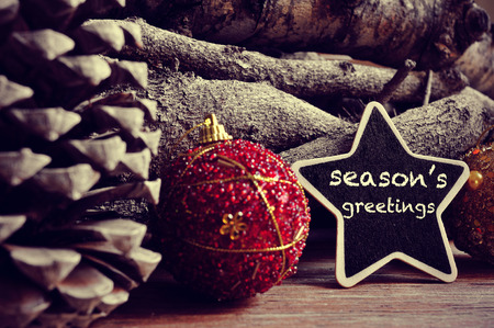 seasons greetings: the text seasons greetings written in a star-shaped blackboard and some christmas balls, pinecones and a pile of logs in the background