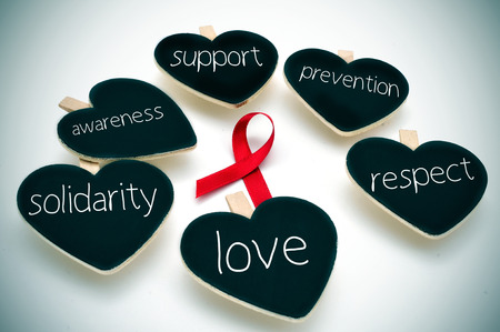 cure prevention: a red ribbon for the fight against AIDS and some heart-shaped blackboards with words such support, prevention, respect, love, solidarity and awareness Stock Photo
