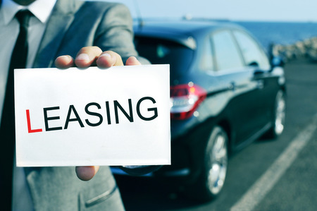car retailer: man in suit holding a signboard with the word leasing written in it, with a black car in the background Stock Photo