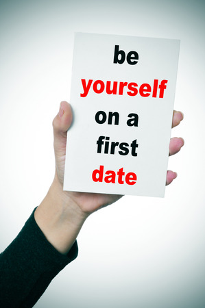 a woman hand showing a signboard with the text be yourself on a first date written in it photo