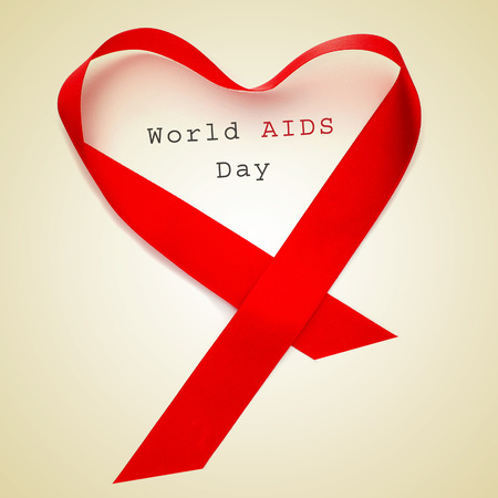 first day: a red ribbon forming a heart and the text world AIDS day on a beige background Stock Photo