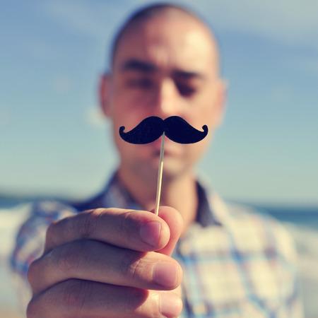 ein junger Mann mit einem falschen Schnurrbart in einem Stock in vor seinem Gesicht