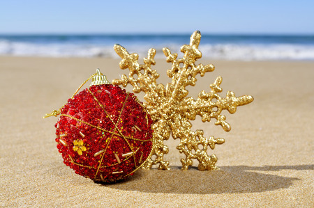 a christmas ball and a star on the sand of a beach photo