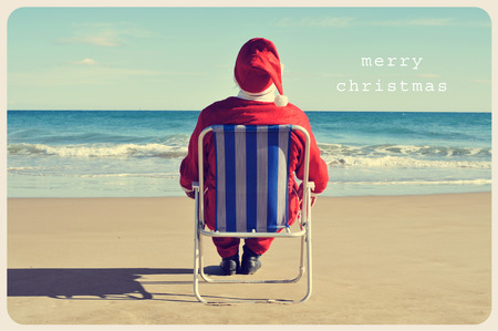 a picture of santa claus sitting in a beach chair on the beach and the text merry christmas like a postcard photo