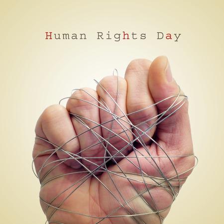 derechos humanos: una mano del hombre atado con alambre y el día de los derechos humanos de texto sobre un fondo beige