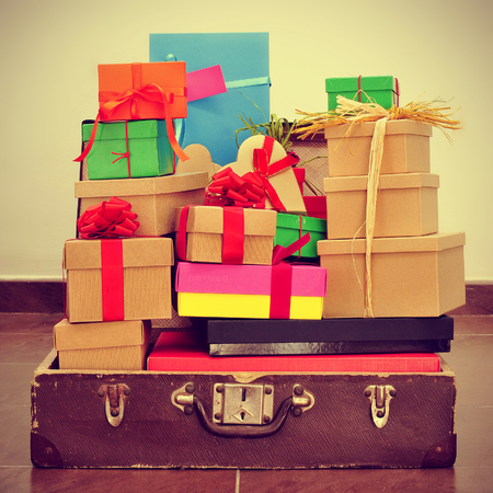 a pile of gifts of different colors and sizes in an old suitcase, with a retro effect photo