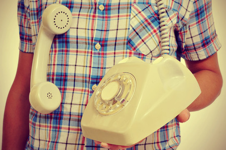 telephone cable: a young man with a rotary dial telephone in his hand, with a retro effect Stock Photo
