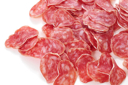 embutido: closeup of some slices of fuet, spanish cured sausage typical of Catalonia, on a white background