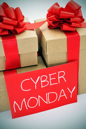 a pile of gifts and the text cyber monday written in white in a red signboard Stock Photo