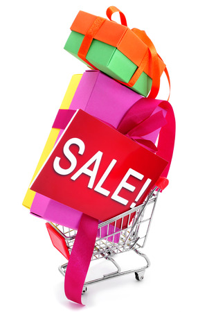 a pile of gift boxes of different colors and a signboard with the word sale in it in a shopping cart, on a white background photo