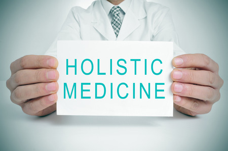 prescription medicine: a doctor showing a signboard with the text holistic medicine written in it