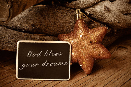 god bless: the text god bless your dreams written in a blackboard and a christmas star and a pile of logs in the background Stock Photo