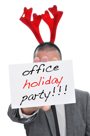 office party: a man in suit with a reindeer antlers headband holding a signboard with the text office holiday party written in it Stock Photo