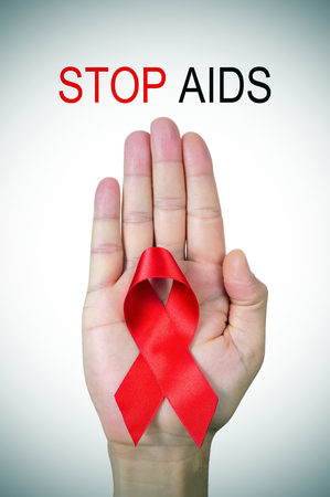 the text stop AIDS and a red ribbon in a man hand photo
