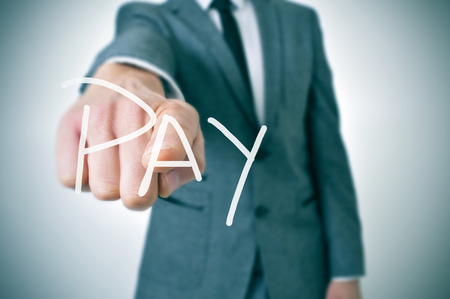 commandment: man in suit pointing the finger to the word pay written in the foreground