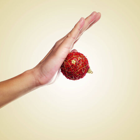 a man hand with a red christmas ball on a beige background, with a retro effect photo