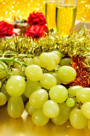 racimos de uvas: primer plano de un racimo de uvas y vasos de champ�n y algunos regalos en el fondo de la tradicional celebraci�n del A�o Nuevo en Espa�a