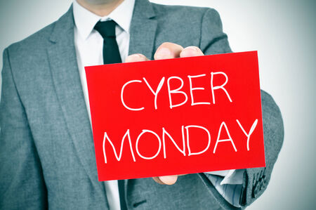 a man in suit showing a red signboard with the text cyber monday written in it
